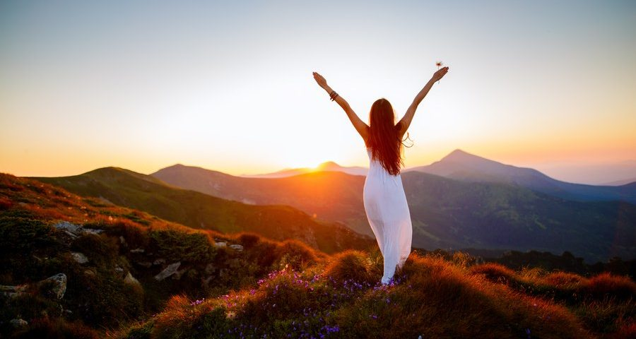 Woman in a white dress welcoming the sunset druing her heroine's journey quest